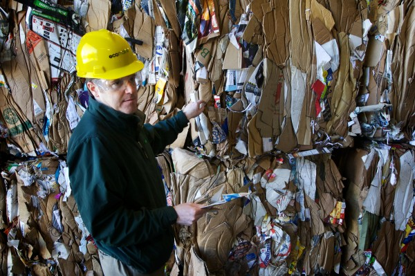 Kevin Roche, general manager of ecomaine, a recycling and trash-to-energy facility in Portland, stands in front of a bale of recyclable cardboard material.