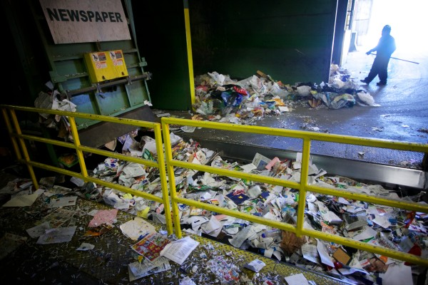 A worker at ecomaine in Portland presorts paper before it is bailed for recycling.