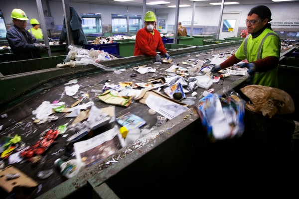Workers at ecomaine sort recyclable materials at the plant in Portland.