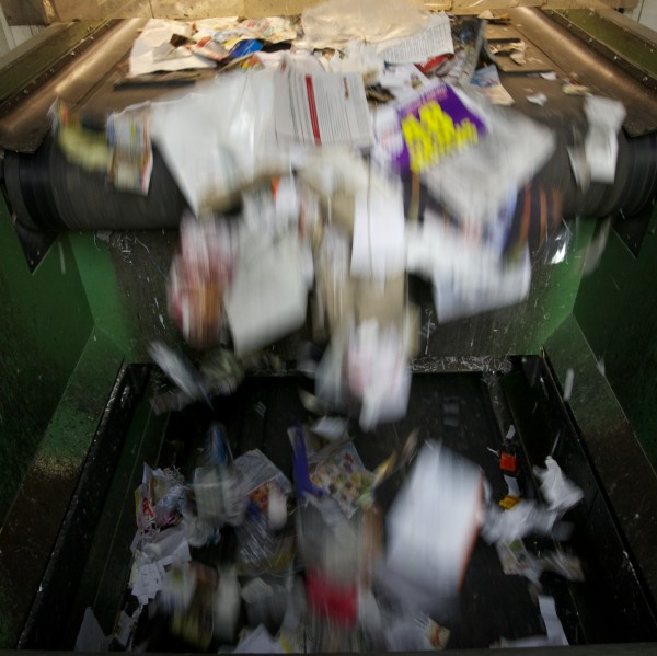 Recyclable material drops off a conveyor belt at ecomaine in Portland.