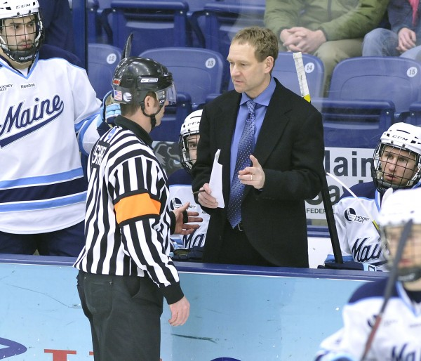 Maine hockey coach Tim Whitehead asks official Kevin Shea why they were assessed a penalty on the opening faceoff an NCAA college hockey game against Merrimack in Orono on March 10, 2012