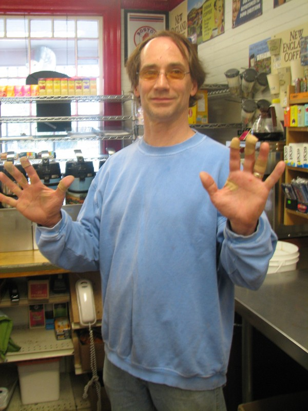 Richard Simis, owner of the Town Hill Market in Bar Harbor, holds up his hands Wednesday morning to show bandages covering cuts he suffered while wrestling with a robber in the store hours earlier. Simis overpowered the robber and held him until police arrived.