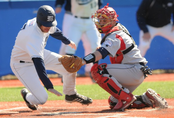 UMaine's Nick Bernardo (left) twists around Stony Brook catcher Anthony Italiano as he reaches for home plate during ninth-inning action on Sunday at Orono. Italiano had already tagged him as he approached the plate and Bernardo was called out. Stony Brook won the game 1-0.