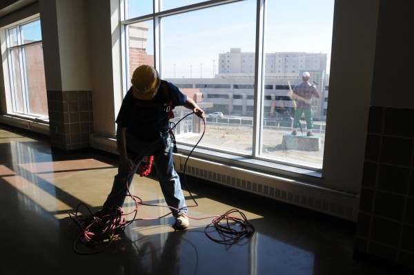 Service Master employee Manuel DaSilver untangles a electrical cord on the second floor of the new Cross Insurance Center in Bangor on Friday. Paul Bunyan can be seen facing Main Street in the background. Cleaners mopped floors and wiped down seats at the center in preparation for a soft opening in June.
