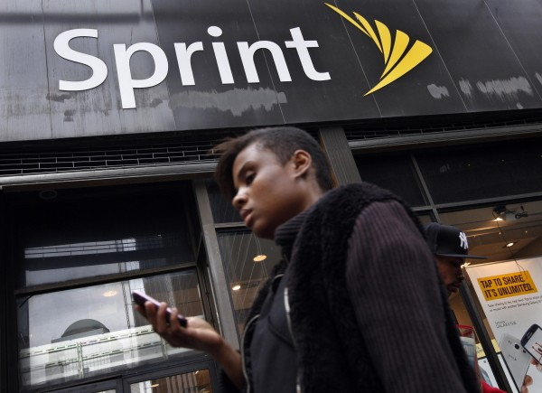 A woman walks past a Sprint store in New York's financial district in this file photo taken October 15, 2012. Dish Network Corp., the No. 2 U.S. satellite television provider, offered to buy Sprint Nextel Corp. for $25.5 billion in cash and stock, a move that could thwart the proposed acquisition of Sprint by Japan's SoftBank Corp.