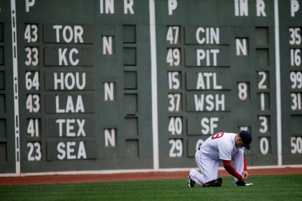 Red Sox left fielder Daniel Nava ties his shoe in front of the scoreboard Saturday at Fenway Park.