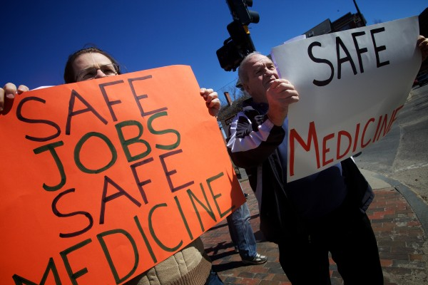Ben Collings (left) and Wayne Poland take part in a demonstration in Portland on Saturday morning supporting unionizing efforts at Wellness Connection of Maine, a medical marijuana dispensary.