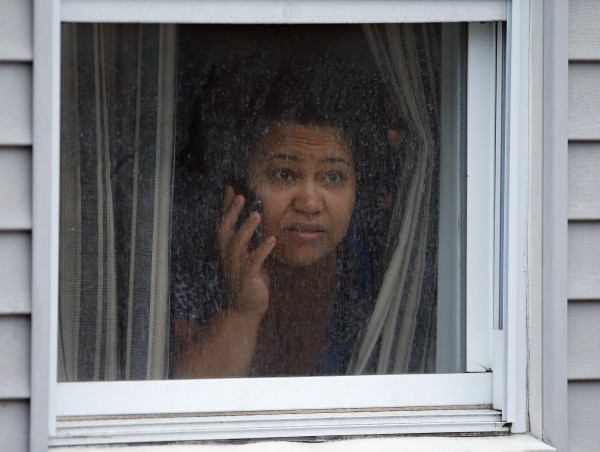 A woman watches police as they search for the Boston Marathon bombing suspects in Watertown, Massachusetts April 19, 2013.  Police on Friday killed one suspect in the Boston Marathon bombing during a shootout and mounted a house-to-house search for a second man in the suburb of Watertown after a bloody night of shooting and explosions in the city's streets.