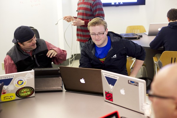 Derek O'Brien (left) shares a laugh with Chris Protzmann during their senior capstone class at  University of Maine in Orono. O'Brien is quadriplegic and will be graduating from the school's new media program in May.