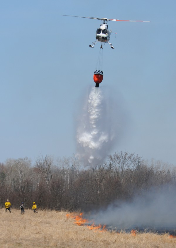 A helicopter drops water on the edge of a 7-acre grass and woodlands fire in Bradford on Monday. The fire was started by a farmer with a permit but got out of control when winds picked up. Numerous departments responded and are on scene at this time putting out hot spots in the woods.