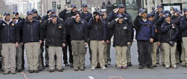 FBI officers stand near the site of the Boston Marathon finish line on Boylston Street during ceremonies symbolically releasing jurisdiction over to the city in Boston, Massachusetts, April 22, 2013.