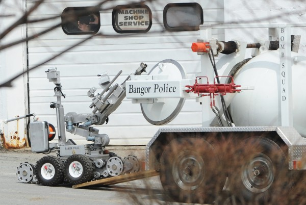 A Bangor police robot moves a hand grenade into a containment vessel on Davis Street in Bangor on Tuesday. Traffic on Main Street was stopped for five minutes as the robot performed its task. The grenade will be transported to the police department's disposal site, where it will be detonated using explosives.