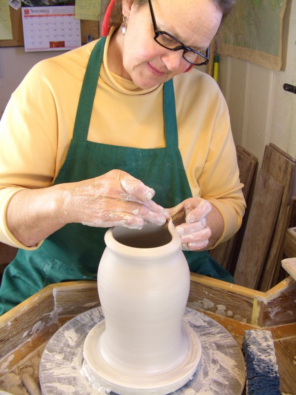 April Adams, owner of Columbia Falls Pottery, works on a vase in her studio. Adams recently opened her second store in Washington County, in Machias.