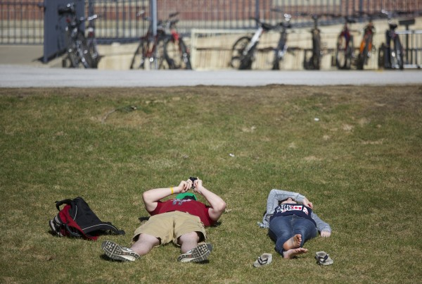 Trey Stewart (left), a freshman political science major, and Hope Milne, a freshman music education major, lay on a lawn at the University of Maine in Orono Wednesday afternoon. Temperatures reached the mid-50s and according to the National Weather Service will increase to the high 60s on Friday with showers possible for the weekend.