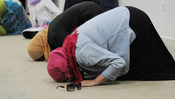 Muslim women pray at the Islamic Center of Maine in Orono on Saturday  before a potluck dinner. The Center hosts the dinner to encourage non-Muslims to learn more about the their faith.
