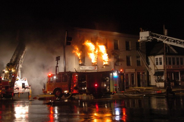 Flames tear through the second floor of the building at the corner of Mason and Maine streets in the early morning hours of April 17, 2011.