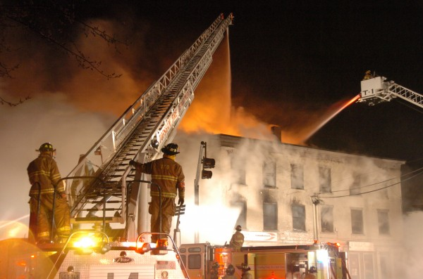 Firefighters pour water onto the flames at 45 Maine St. on April 17, 2011. The three-alarm fire drew about 100 firefighters from 10 communities, ruined 5 businesses and displaced 17 tenants, but no injuries were reported.