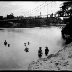 "Swimmers and Swinging Bridge, Topsham, Androscoggin River, Maine, 2012"" is a unique ambrotype that's part of Brunswick photographer Michael Kolster's photographic work documenting the rise and fall of American rivers, including the Androscoggin River. Kolster was selected as a 2013 Guggenheim Fellow for his work."