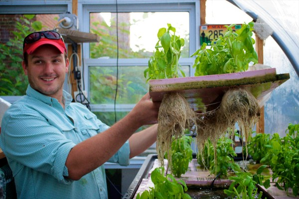 Tyler Gaudet of Fluid Farms holds a raft of herbs grown in their small facility in Portland in this undated photo. The operation, which grows fish as well, is moving to a larger venue in North Yarmouth with the help of a Kickstarter campaign.