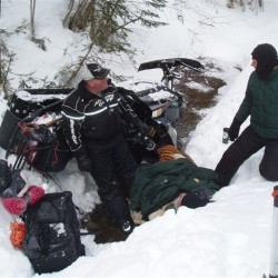 Snowmobiler survives 20 cold hours trapped under his sled