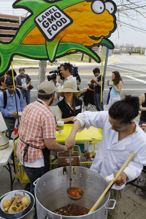 Servers Austin Ginsberg and Jonathan Bisagni feed soup to fellow protesters during an eat-in in front of the U.S. Food and Drug Administration's Center for Food Safety and Applied Nutrition in College Park, Maryland April 8, 2013.  The protesters are demanding for Genetically Modified Foods (GMO) to be labelled and tested long-term on human beings before being approved.
