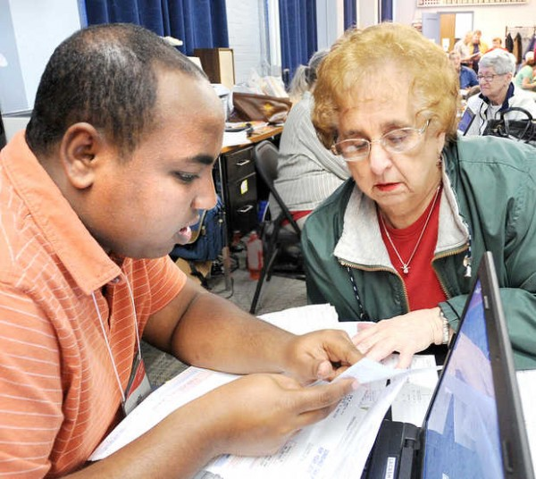 Abdisalan Mohamed Ali of Lewiston helps Stella Bard of Auburn file her tax return Friday, March 22, at the Lewiston Armory. Ali is a student at the University of Southern Maine earning college credit for volunteering with the L-A CA$H Coalition and AARP, which offer free tax assistance to low-income households.