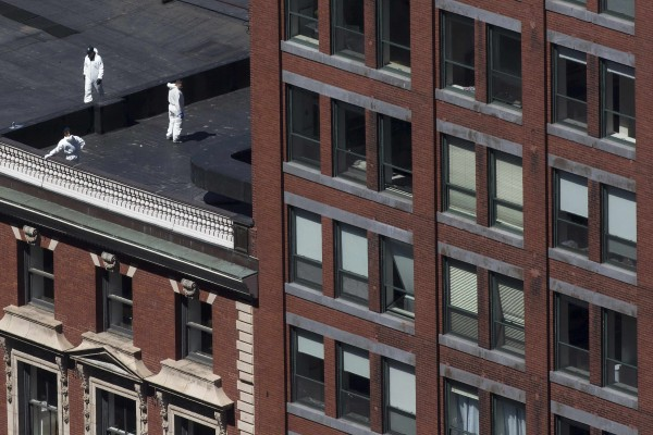 Officials investigate a rooftop Wednesday after two explosions hit the Boston Marathon on Monday.