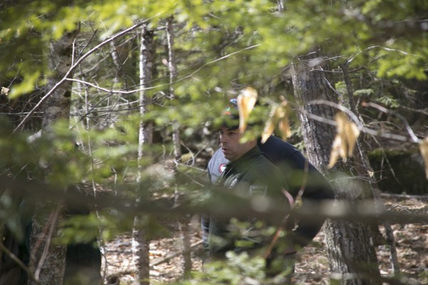 Sgt. Terry Hughes Jr. of the Maine Warden Service waits with other law enforcement officers near the campsite of Christopher Knight. Law enforcement was in the process of collecting evidence and the landowner did not allow media to enter the site.