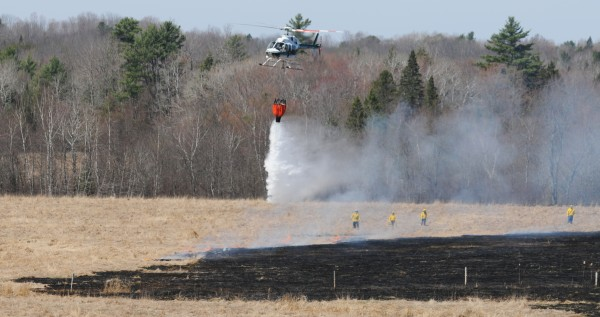 A helicopter drops water on the edge of a 7-acre grass and woodlands fire in Bradford on Monday.
