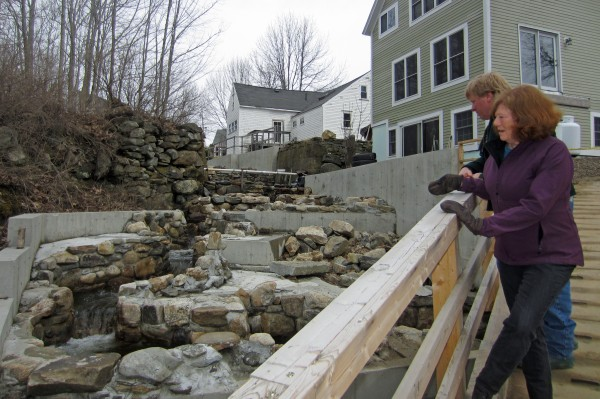 Deb Wilson and Mark Becker look out over a portion of the restored Damariscotta Mills fish ladder. Although the restoration is not yet complete, Wilson said Sunday that the alewives -- due any day -- will &quotgo like wildfire&quot up the new ladder.