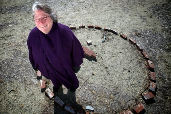 Rev. Sylvia Stocker stands in a circle of bricks on the vacant lot where her church used to stand. The bricks are all that's left of the Universalist Unitarian Church of Brunswick but her congregation will soon get a new building.
