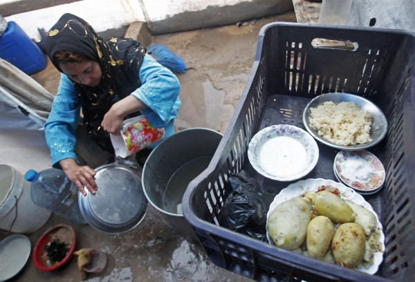 A Syrian woman washes dishes at a refugee camp in the city of Tyre, in southern Lebanon in this January 31, 2013 file photo.