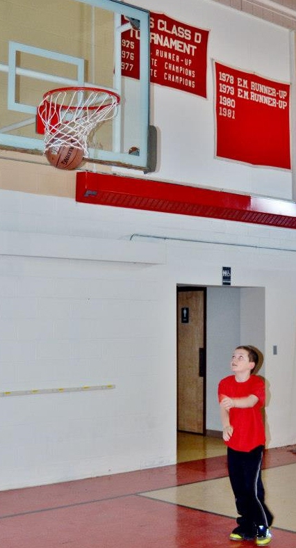 An Allagash youngster plays some hoops in the school's old gym under the sports banners of teams dating back decades.