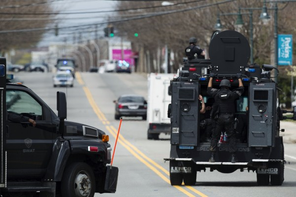 Tactical vehicles full of law enforcement officers drive through the search area for Dzhokar Tsarnaev, the one remaining suspect in the Boston Marathon bombing, in Watertown, Mass., on April 19, 2013.