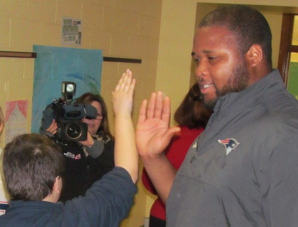 New England Patriots offensive lineman Marcus Cannon gives students departing from a Thursday morning assembly at Lincoln Middle School in Portland high fives. During the event, Cannon talked about the importance of healthy eating and exercise.