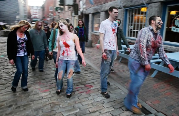 Zombies stagger down Wharf Street in Portland Tuesday while on a pub crawl in the Old Port.