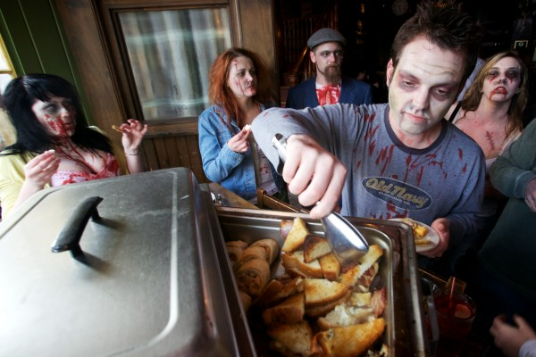 Sam Barron samples the happy hour fixings at Bull Feeney's in Portland Tuesday while on a pub crawl with friends dressed as zombies.