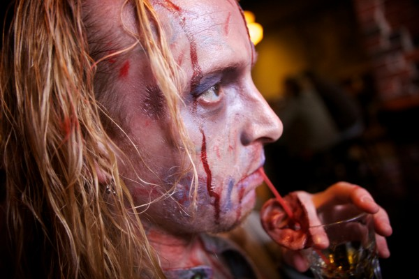 Jim Roberts, organizer of the zombie pub crawl, sips a drink through a straw decorated with a rubber ear at Bull Feeney's in Portland Tuesday. Other pub crawl themes pulled off by the same group of friends include superheroes and villains.