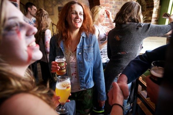 Kelsey Woods (left) and Lindsay Roberge (center) enjoy a zombie pub crawl in Portland Tuesday.