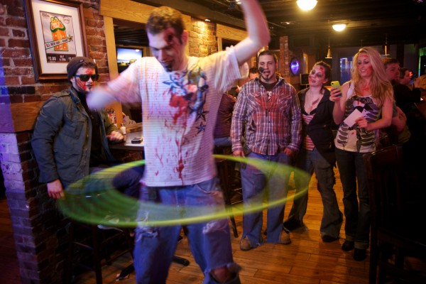 A zombiefied Ben Blaisdell competes in a hula hoop competition while on a zombie pub crawl in Portland Tuesday.