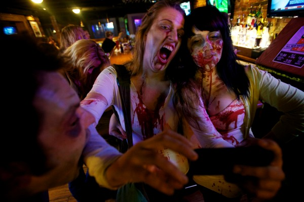 Sam Barron tries to take a bite out of Caitlin French as she takes a picture of herself and Amy Baillargeon while in zombie attire at Pat's Pizza in Portland Tuesday.