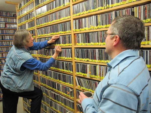 Pat Fowler files CDs at the WERU on-air library, while station manager Matt Murphy looks on.