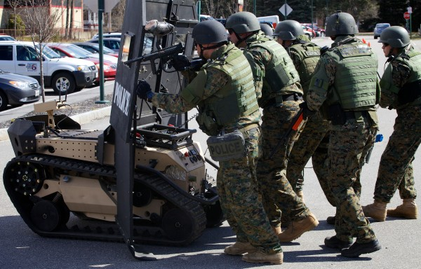 Members of the Southern Maine Special Response Team crouch behind Howe and Howe Technologies' remote tactical approach vehicle at the Sanford Police Department Thursday. Known as the &quotSWAT BOT,&quot the vehicle is designed to be bullet and explosive resistant and can be controlled remotely.