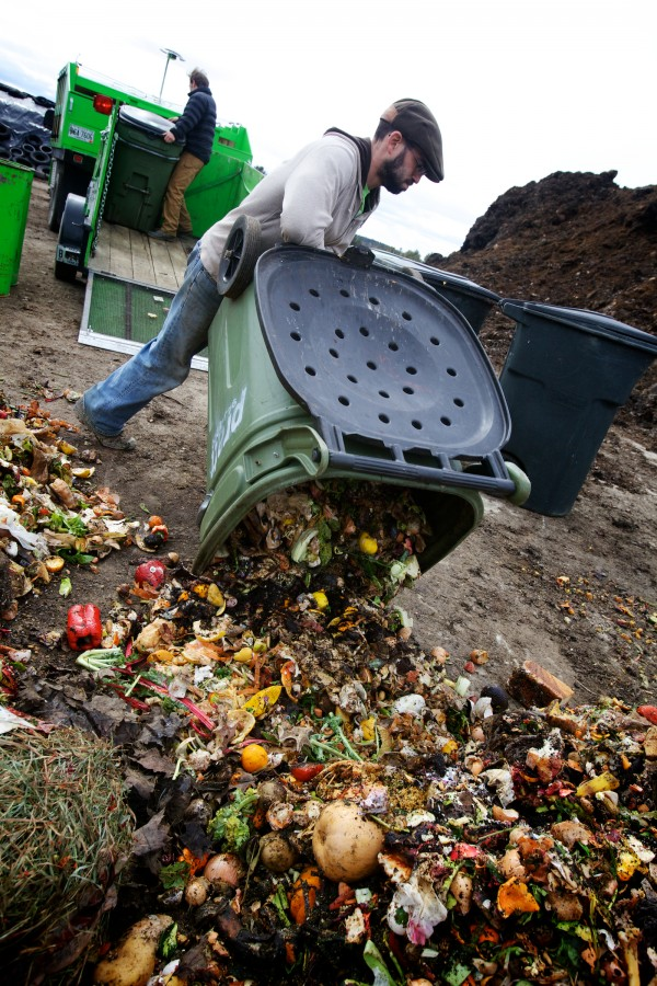 Cory Fletcher (right) and Tyler Frank of Garbage to Garden empty barrels of food scraps at Eddie Benson's dairy farm in Gorham Wednesday afternoon where the scraps will be turned into compost.