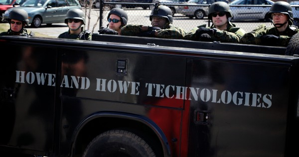 Members of the Southern Maine Special Response Team rest after taking part in a demonstration of Howe and Howe Technologies' remote tactical approach vehicle at the Sanford Police Department Thursday. Known as the &quotSWAT BOT,&quot the vehicle is designed to be bullet and explosive resistant and can be controlled remotely.