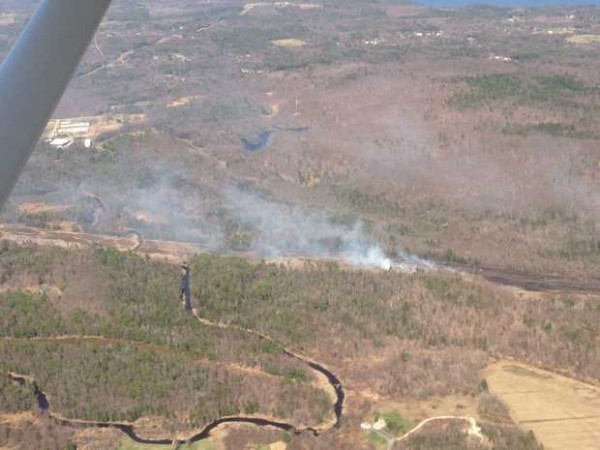The Maine Forest Service and multiple municipal fire departments fought a massive, fast-moving woods fire off College Street in Lewiston on Tuesday.