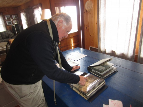 Fred Hill, in his family's cottage on Popham Beach, looks through a scrapbook of news clippings about erosion dating back to the early 1900s.