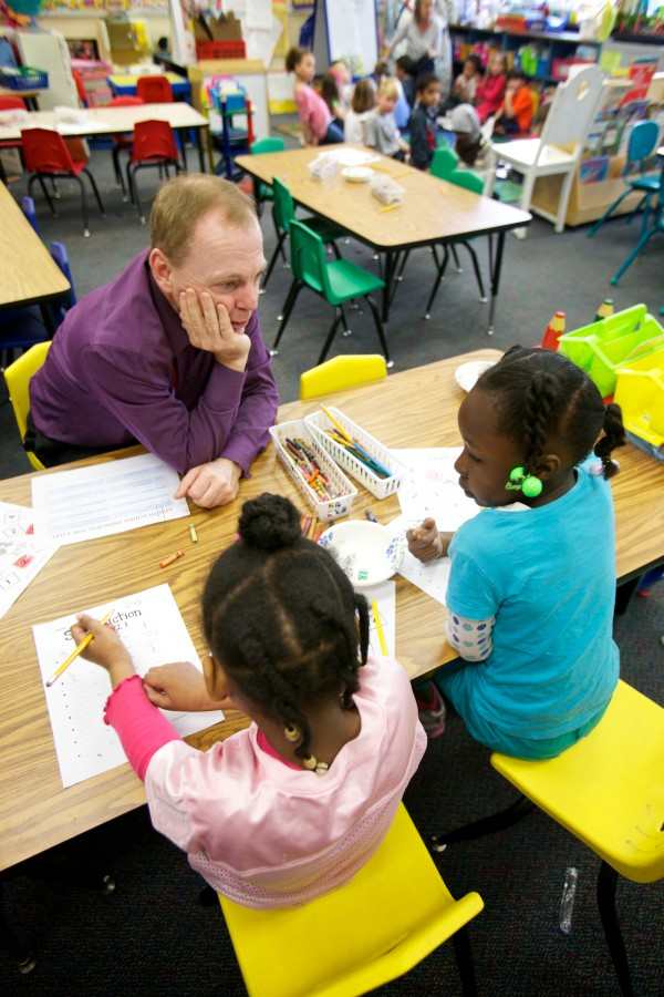 Mark McAuliffe, managing partner of Apothecary by Design Pharmacy, works with kindergartners Annalisa McPherson, 5 (left) and Elianne Ywmomo, 6 at Lyesth Elementary School in Portland Monday morning. McAuliffe was visiting as part of the Portland Public Schools and Portland Regional Chamber of Commerce's Principal for a Day program.