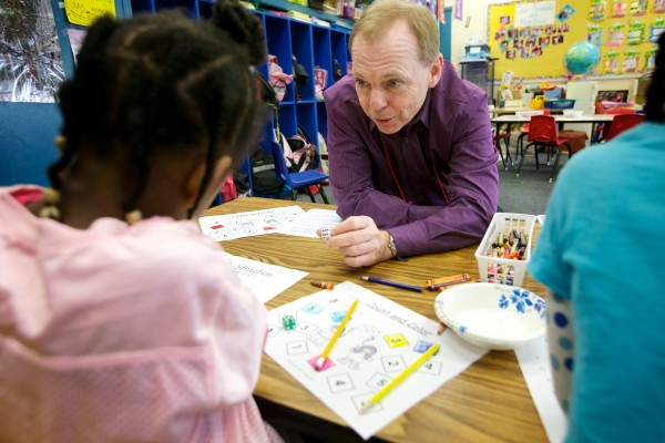 Mark McAuliffe, managing partner of Apothecary by Design Pharmacy, works with kindergartners Annalisa McPherson, 5 (left) and Elianne Ywmomo, 6, at Lyesth Elementary School in Portland Monday morning. McAuliffe was visiting as part of the Portland Public Schools and Portland Regional Chamber of Commerce's Principal for a Day program.