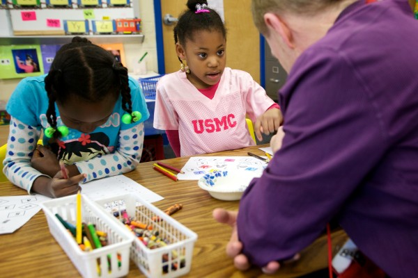 Mark McAuliffe, managing partner of Apothecary by Design Pharmacy, works with kindergartners Elianne Ywmomo, 6 (left) and Annalisa McPherson, 5, at Lyesth Elementary School in Portland on Monday morning. McAuliffe was visiting as part of the Portland Public Schools and Portland Regional Chamber of Commerce's Principal for a Day program.
